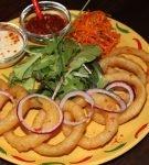 луковые кольца и соусы на блюде