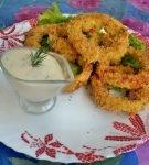 луковые кольца на тарелке с соусом