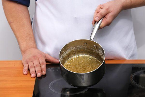 Кастрюлька с сиропом в руках повара
