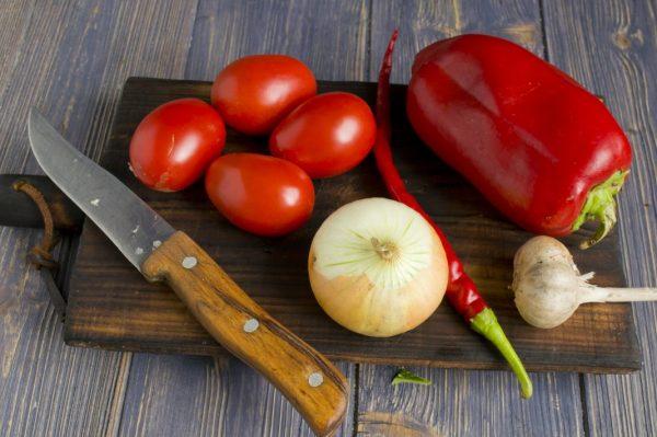Овощи, нож и разделочная доска на столе