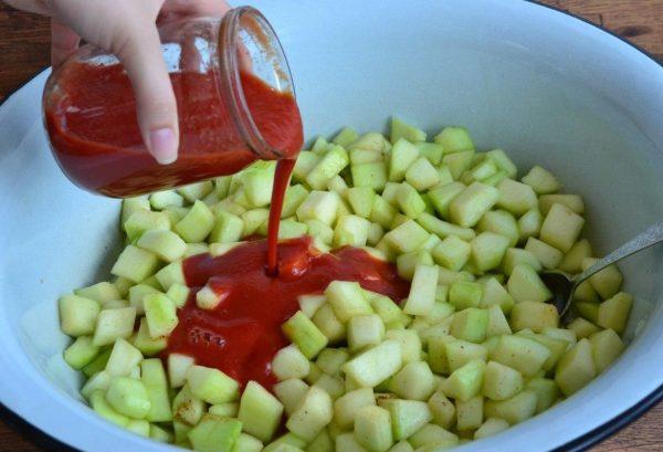 Добавление томатного соуса в таз с нарезанными кабачками