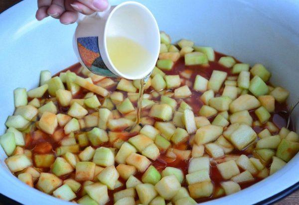 Кабачки в томатном соусе и растительное масло в чашке