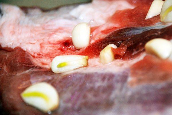 Мясо и разрезанные на кусочки зубчики чеснока
