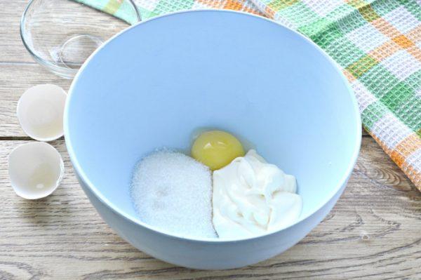 Яичный желток, сахар и сметана в голубой миске