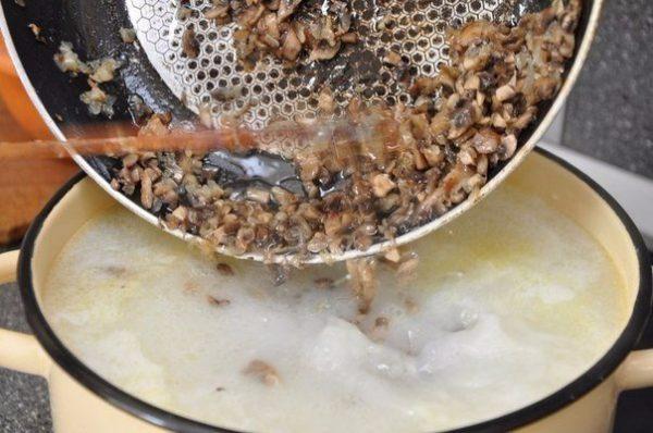 Добавление обжаренных грибов с луком в кастрюлю с супом