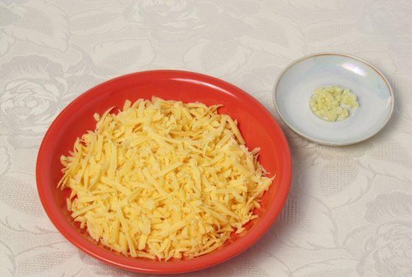 Тёртый сыр в миске и рубленый чеснок на блюдце