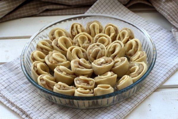 Заготовка для пирога «Хризантема» из теста и фарша в круглой форме на столе