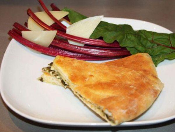 Кусочек осетинского пирога, свекольная ботва и сыр на белой тарелке