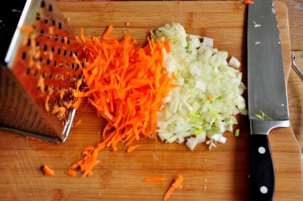 Измельчённые лук и морковь на разделочной доске