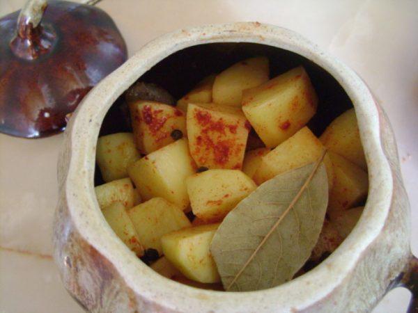 Нарезанный кубиками сырой картофель с лавровым листом и молотой паприкой в керамическом горошочке