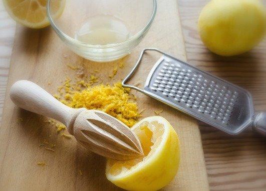 Лимонный сок, цедра, металлическая тёрка и ручная соковыжималка для цитрусовых на столе