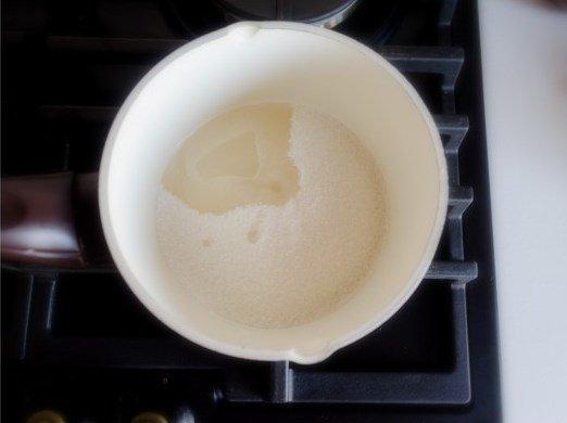 Сахарный песок и вода в маленькой кастрюле на плите