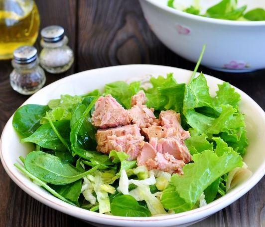 Кусочки консервированного тунца на салатных листьях в тарелке