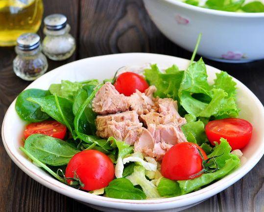Салатные листья, кусочки тунца и половинки черри в большой тарелке