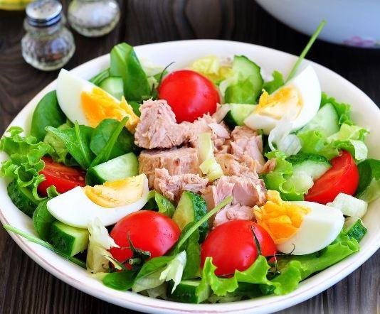 Четвертинки варёных яиц, кусочки тунца и свежих овощей на салатных листьях