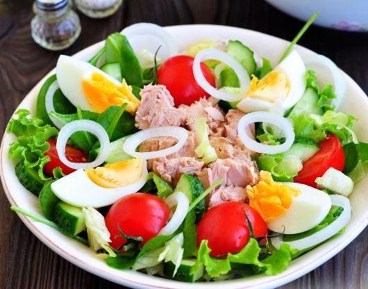 Салат с тунцом, овощами, варёными яйцами и зеленью на тарелке