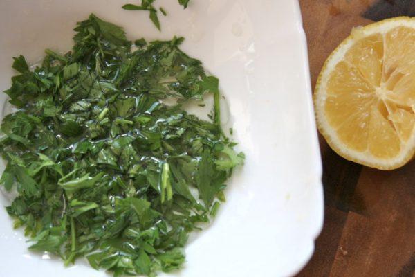 Измельчённая петрушка с маслом в тарелке и половинка лимона