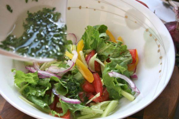 Заправка овощного салата смесью масла, лимонного сока и зелени
