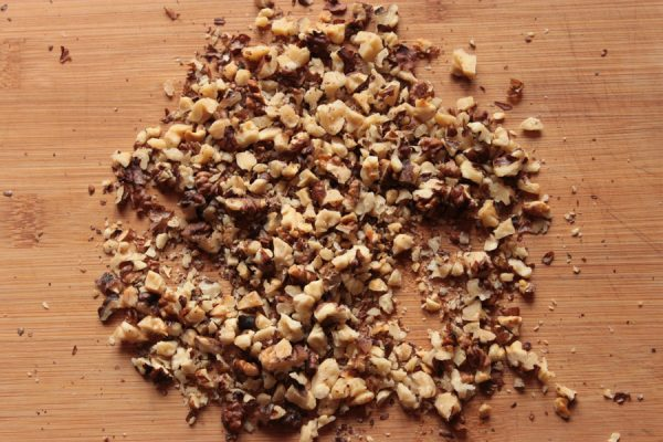 Измельчённые ядра грецких орехов на разделочной доске