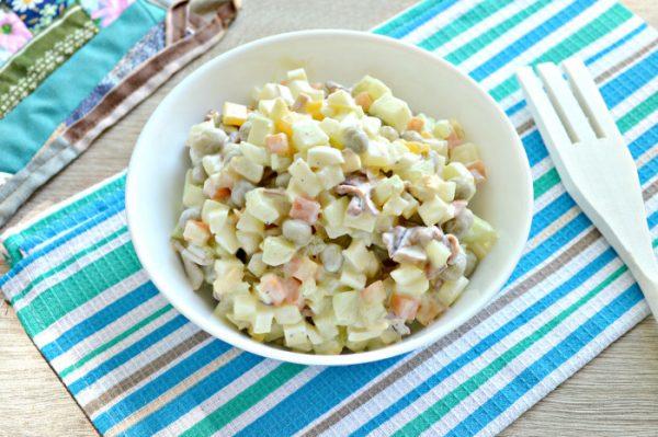 Салат с кальмарами, овощами и яйцами в салатнике