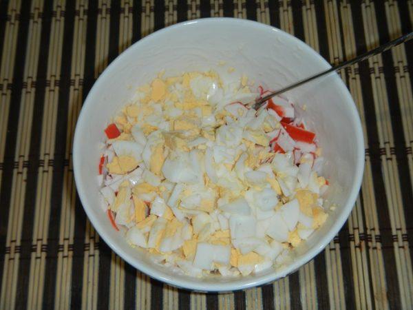 Рубленые варёные яйца в миске с крабовыми палочками и варёным кальмаром