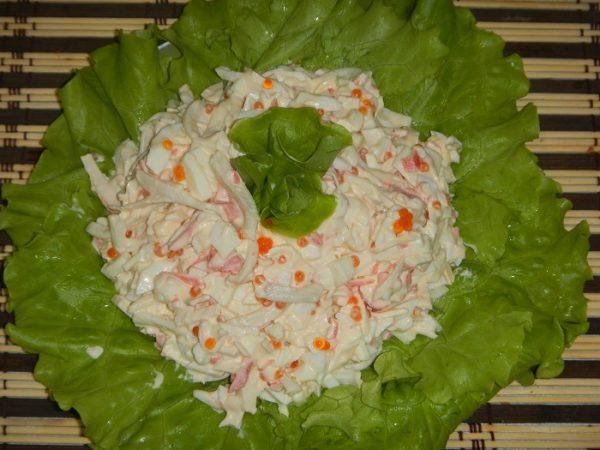 Салат с кальмарами, крабовыми палочками и красной икрой на блюде