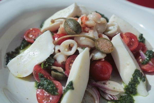 Готовый салат с кальмарами и моцареллой в большой тарелке