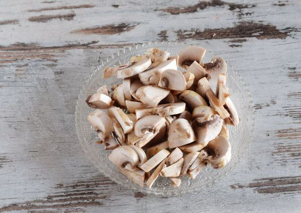 нарезанные пластинами свежие шампиньоны в миске