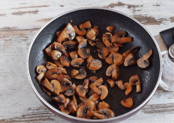 Обжаренные кусочки шампиньонов в сковороде