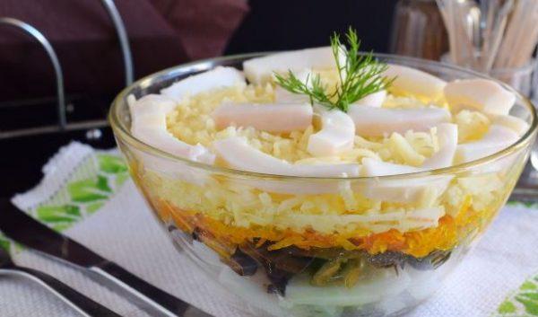 Салат с кальмарами, жареными грибами, сыром и морковью в стеклянном салатнике
