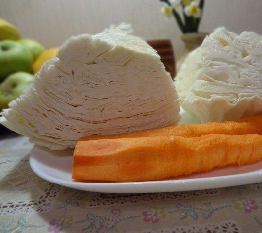 Куски белокочанной капусты и очищенная морковь на тарелке