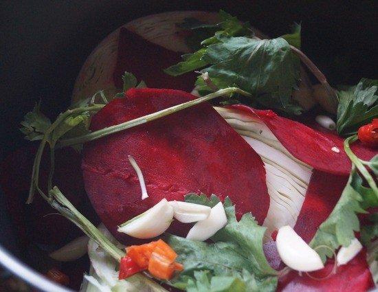 Капуста, свёкла, чеснок, острый перец и зелень в кастрюле