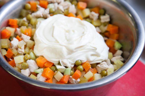 Нарезанные ингредиенты для салата «Столичный» и майонез в миске