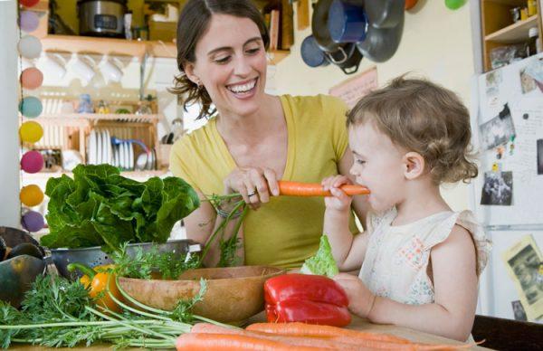 мать кормит ребёнка овощами