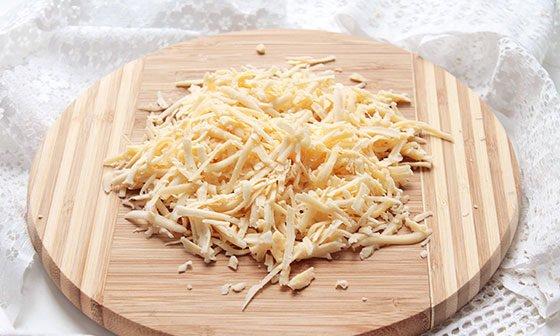 Тёртый твёрдый сыр на круглой разделочной доске