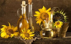 Бутылки с растительным маслом и цветы подсолнуха