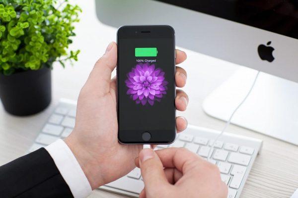 Мужчина держит в руках смартфон со 100% заряда
