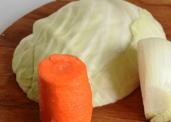 Кусочек свежей капусты, морковь и репчатый лук на разделочной доске