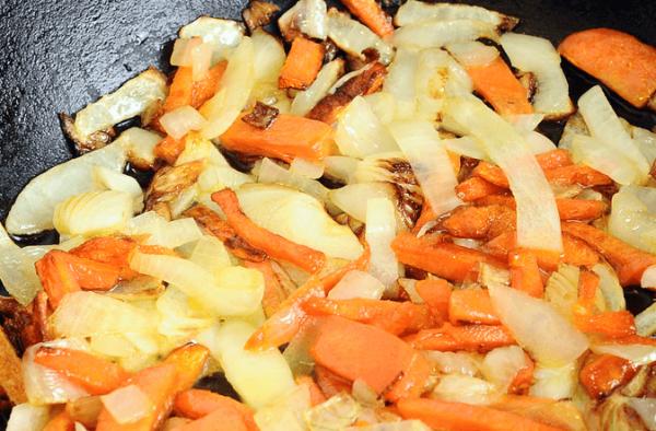 Обжаренный репчатый лук и морковь в сковороде