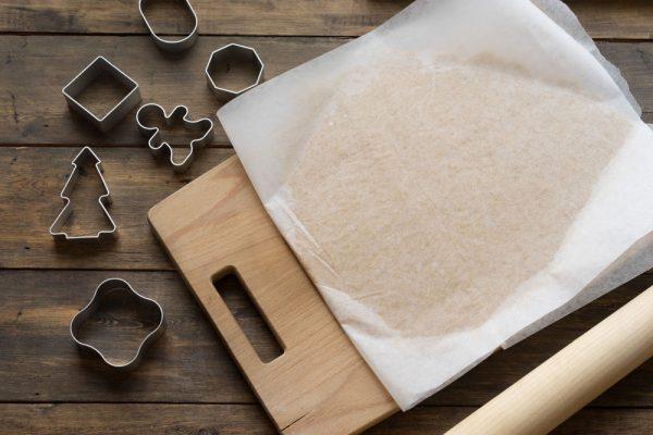 Пласт теста для имбирных прняиков между листами пекарской бумаги и металлические формочки для печенья