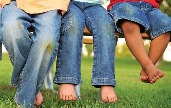 Ноги папы и двух сыновей в джинсах с пятнами от травы на коленках