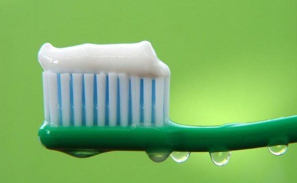 Белая зубная паста на зелёной щётке