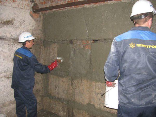 Промазывают подвальные стены мастикой