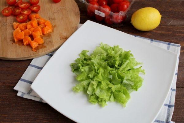 Кусочки салатных листьев на белой квадратной тарелке