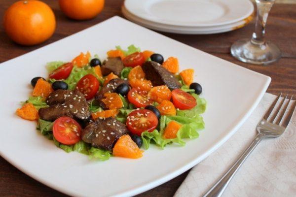Тёплый салат с куриной печенью и мандаринами на тарелке