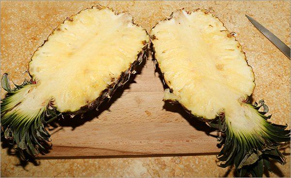 Разрезанный на половины ананас на разделочной доске