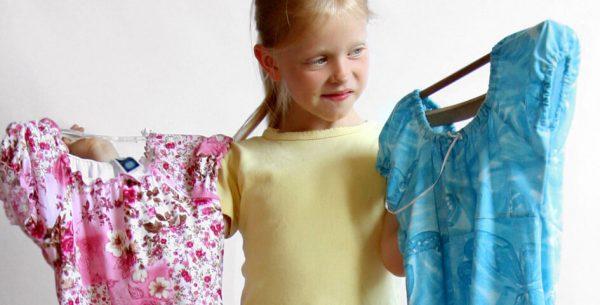 девочка держит платья
