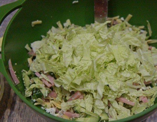Нарезанная полосками пекинская капуста в миске с салатом из ветчины и сыра