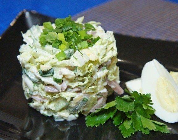 Порция салата «Моника», четвертинки варёного яйца и свежая зелень на чёрной тарелке