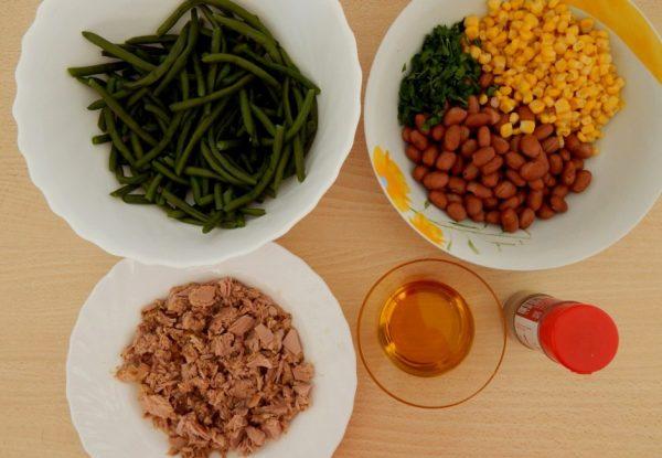 Ингредиента для салата с тунцом и фасолью в разных тарелках на столе